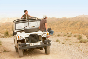 Couple sitting on stationary four wheel drive vehicle in dの写真素材 [FYI03629515]