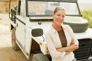 Woman standing in front of four wheel drive car in desertの写真素材 [FYI03629520]