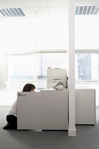 Female office worker kneeling in front of open cabinet inの写真素材 [FYI03629544]