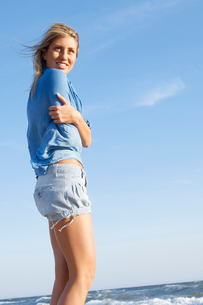 Young cold woman standing in surf on beach  low angle viewの写真素材 [FYI03629563]