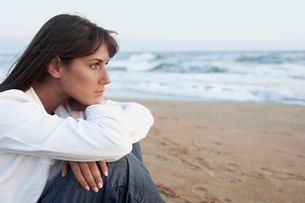Pensive Woman on the Beach looking out to sea  side viewの写真素材 [FYI03629568]
