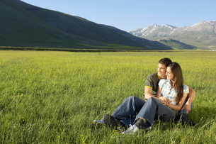 Young couple sitting in mountain field looking at view  fuの写真素材 [FYI03629581]
