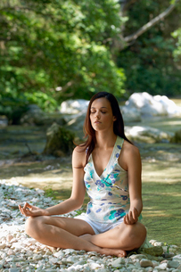 Young woman meditating by forest river  full lengthの写真素材 [FYI03629585]