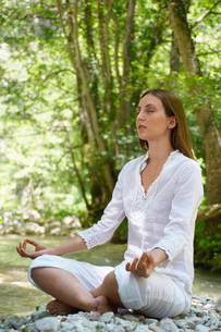 Young woman meditating by forest river  full lengthの写真素材 [FYI03629586]