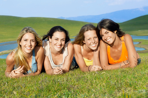 Four young woman lying near mountain lake  portrait  grounの写真素材 [FYI03629593]