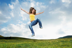 Woman jumping for joy in mountain meadow  front viewの写真素材 [FYI03629594]