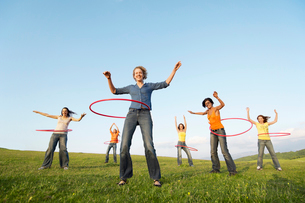 Group of friends using hula hoops in mountain field  low aの写真素材 [FYI03629596]