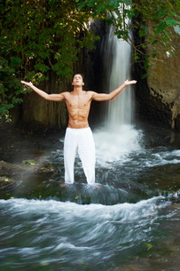 Man standing in river by waterfall meditating  front viewの写真素材 [FYI03629602]