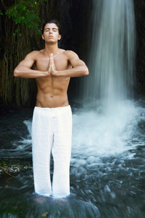 Man standing in river by waterfall meditating  front viewの写真素材 [FYI03629603]
