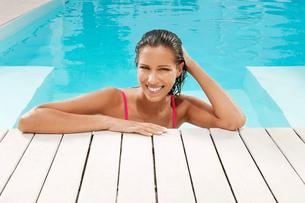 Woman in Swimming Pool resting on poolside  portraitの写真素材 [FYI03629615]