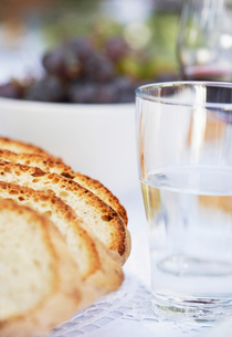 Loaf of Bread and Glass of Water on table  close upの写真素材 [FYI03629641]