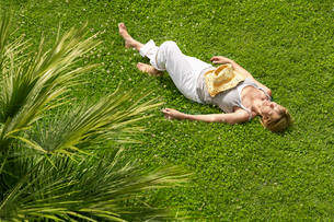 Middle-aged woman sleeping on grass  high angle viewの写真素材 [FYI03629658]