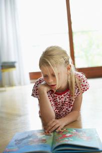 Girl lying on floor at home reading atlasの写真素材 [FYI03629680]