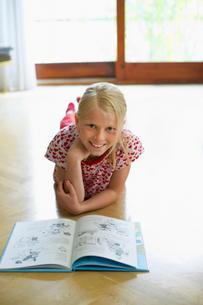 Girl lying on floor at home reading book  portraitの写真素材 [FYI03629684]