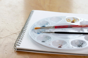 Brushes and palette on sketchbookの写真素材 [FYI03629687]