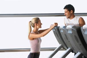 Man and Woman Talking by treadmill in Health Clubの写真素材 [FYI03629775]