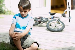Sad little boy sitting on porch of houseの写真素材 [FYI03629822]