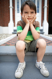 Sad little boy sitting on front steps of houseの写真素材 [FYI03629836]
