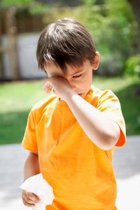 Boy with cold in backyard rubbing eyesの写真素材 [FYI03629842]