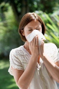 Woman Blowing Nose in gardenの写真素材 [FYI03629846]