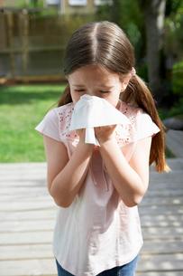 Little girl in backyard blowing noseの写真素材 [FYI03629864]