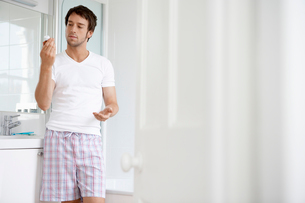 Man in bathroom reading label of pill bottleの写真素材 [FYI03629872]