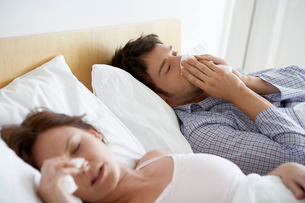 Couple with Colds Lying in Bedの写真素材 [FYI03629877]