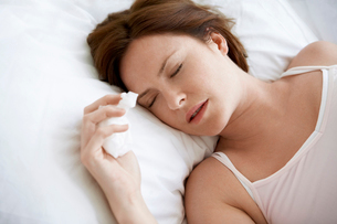 Woman lying in bed with cold  close upの写真素材 [FYI03629879]