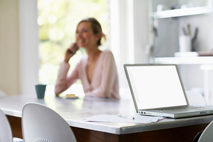 Woman on phone sitting at kitchen table by laptop  focus oの写真素材 [FYI03629895]