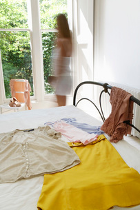 Woman walking by outfit laid out on bedの写真素材 [FYI03629899]