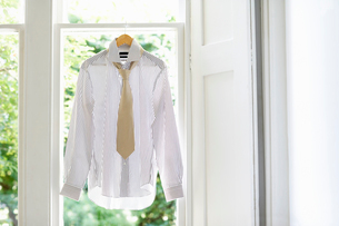 Dress shirt and tie on hanger in domestic windowの写真素材 [FYI03629900]