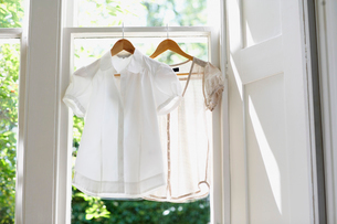 Two blouses on Hangers in domestic windowの写真素材 [FYI03629904]