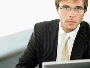 Businessman sitting at office desk  portraitの写真素材 [FYI03629920]