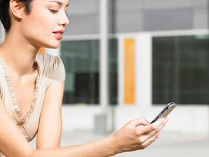 Young woman sitting in plaza sending text message  close uの写真素材 [FYI03629934]