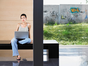 Young woman sitting down using laptop indoors  portraitの写真素材 [FYI03629954]