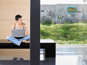 Young woman sitting down using laptop indoorsの写真素材 [FYI03629956]
