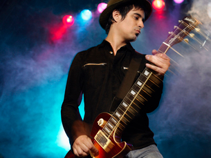 Rock Guitarist on stage in Concert  low angle view  frontの写真素材 [FYI03629970]