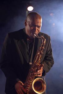 Jazz musician playing saxophone on smokey nightclub stageの写真素材 [FYI03630021]