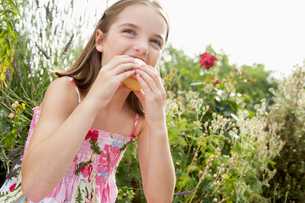 Young girl sitting in meadow eating cupcake  close upの写真素材 [FYI03630029]