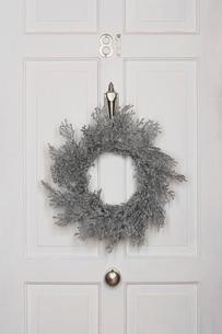 Christmas wreath hanging on white doorの写真素材 [FYI03630064]