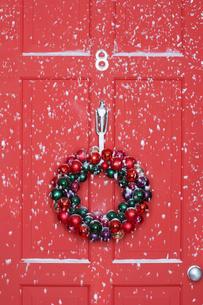Christmas wreath hanging on door  with snowfallの写真素材 [FYI03630065]