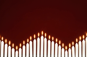 Row of lit candles  on black backgroundの写真素材 [FYI03630066]
