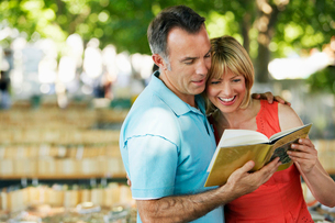 Mid-adult couple in park looking at book togetherの写真素材 [FYI03630111]