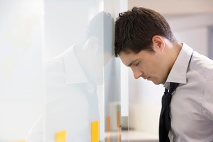 Unhappy Businessman resting head against office wall  sideの写真素材 [FYI03630116]
