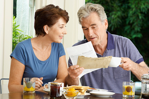 Middle-aged couple looking at bill over breakfastの写真素材 [FYI03630145]