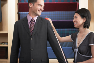 Seamstress measuring businessmans suit in clothes storeの写真素材 [FYI03630164]