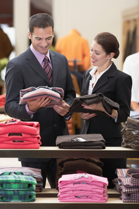 Salesperson assisting businessman in clothes storeの写真素材 [FYI03630167]