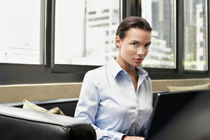 Business woman sitting on sofa using lap topの写真素材 [FYI03630168]