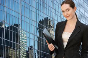 Businesswoman holding portfolio outside office building  pの写真素材 [FYI03630175]