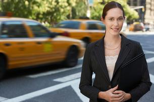 Businesswoman holding portfolio in street  portraitの写真素材 [FYI03630177]